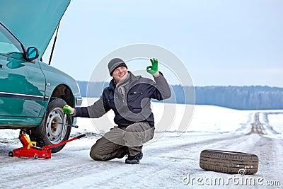 Driver repairing car at the road