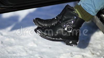 Driver shaking the snow off her feet stock footage