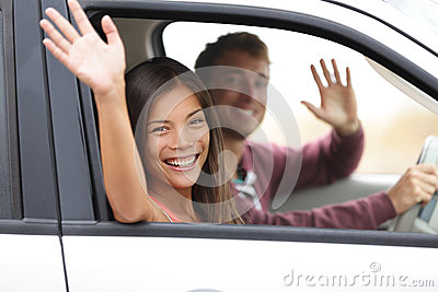 Drivers driving in car waving happy at camera