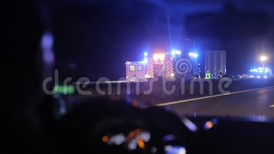 Driving by a car crash on highway at night. View from inside the car. A car passing by a serious car accident on driveway at night. View from inside the car stock video