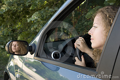 Driving woman reflecting in rear mirror