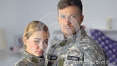 Droevig paar van Amerikaanse militairen die cameraclose-up, gevaarlijk beroep kijken stock video