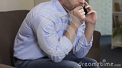 Droevige mannelijke zitting op bank en het spreken op cellphone met ex-meisje, crisis stock videobeelden