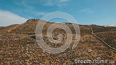 Droge grondheuvel met stenen en keien, dorre struiken, stoffige wegen en ruïnes stock video