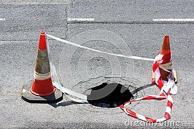 Drogowa dziura z ostrzeżenie rożkami