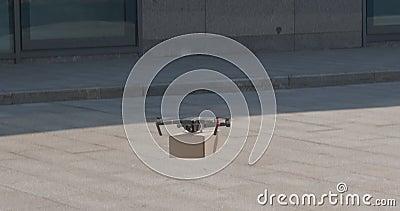 Drone courier som flyger upp med kartong i staden arkivfilmer