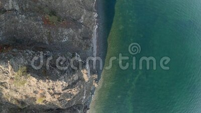 Drone flying above the coastline of sea. Aerial view, top down. Drone flying above the coastline of sea. Aerial view of Lake Baikal shoreline top down stock footage