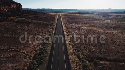 Drone flying forward over straight desert highway road in USA wilderness near massive rocky mountain and beautiful sky. Amazing aerial view of empty stock video footage