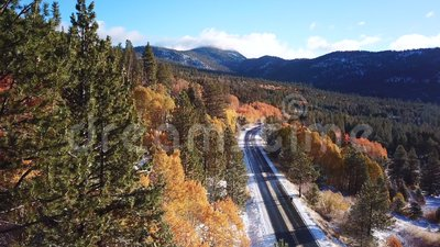 Drone footage of a snowy mountain road in fall at sunrise stock video footage
