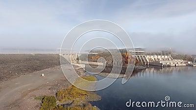 Drone-Kamera nähert sich einem geschlossenen Damm an einem ruhigen Fluss an einem klaren Herbsttag stock video