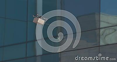 Drone med postpaket som flyger genom glasbyggnader arkivfilmer