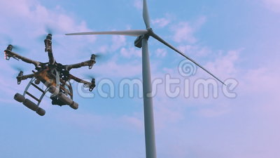 Drone takes off from the hands of a girl near a wind turbine, slow motion. Drone takes off from the hands of a girl near a wind turbine at sunset, slow motion stock footage