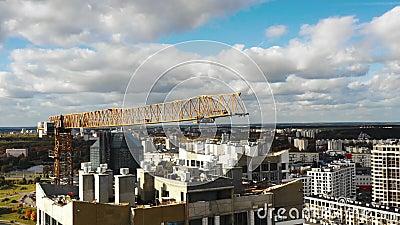 Drone voando muito perto em torno da grua de construção amarela durante o processo de desenvolvimento de blocos torres de alto au vídeos de arquivo