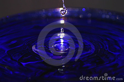 Drops of Water Splashing in a Blue Pool Stock Photo