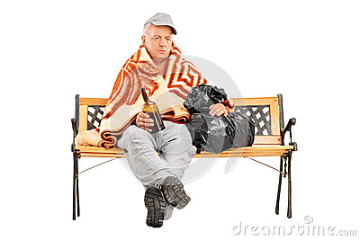 Drunk homeless mature man sitting on a bench with bottle