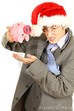Drunk young man in Christmas hat with piggy bank