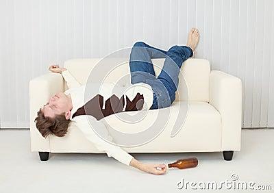 Drunkard sleeps on sofa in an amusing pose