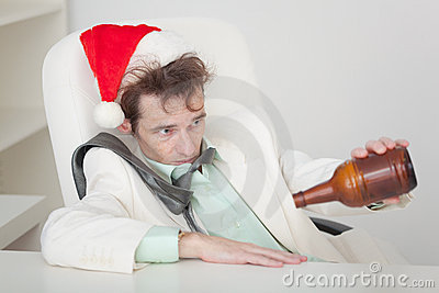 Drunken person in Christmas cap with bottle