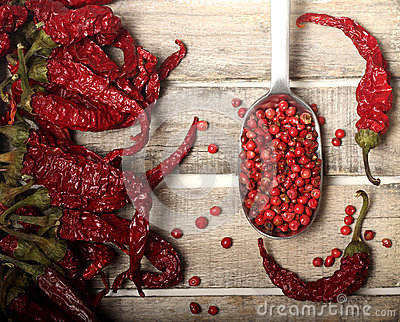 Dry pepper and grains on wooden background