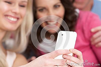 Duas amigas que olham retratos em Smartphone