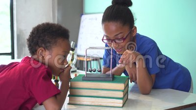 Duas crianças misturadas afro-americanos que usam uma lupa e puxando o balanço da bola dos berços de um newton na sala de aula da vídeos de arquivo