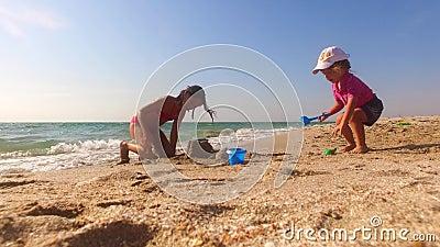 Duas crianças que constroem o castelo da areia na praia filme