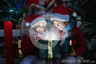Duas crianças que abrem o presente do Natal