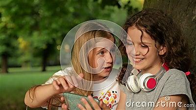 Duas estudantes pequenas que usam o smartphone Crian?as que jogam, leitura, olhando o telefone Povos, crian?as, tecnologia vídeos de arquivo