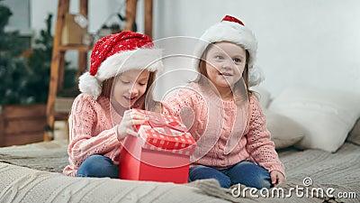 Duas garotas felizes no chapéu de Papai Noel surpreendentes abrindo a caixa de presentes de Natal tendo emoção positiva filme