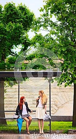 Duas meninas no paragem do autocarro