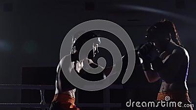 Duas meninas nos capacetes encaixotam seus braços e pés no anel na obscuridade Movimento lento filme