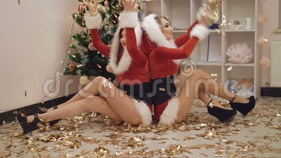 Duas meninas que lanç confetes dourados no partido de ano novo em 4K vídeos de arquivo