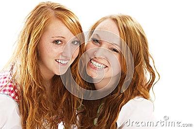 Duas meninas vestidas bávaras do redhead feliz