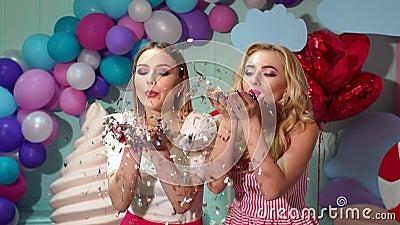 Duas moças que fundem em confetes ou em ouropel no fundo colorido brilhante video estoque