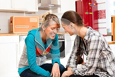 Duas mulheres com a caixa movente em sua casa