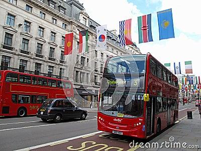 Dubbel däckarebuss i härska gata Redaktionell Fotografering för Bildbyråer