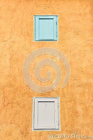 Dubbele vensters op gele muur