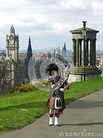 Dudelsackpfeifer in Edinburgh, über dem Stadtbild Redaktionelles Bild
