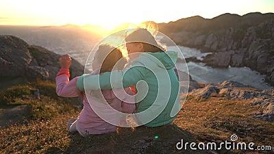 Due bambine ammirano il tramonto o l'alba che si siede sulle rocce costiere sulla spiaggia nordica stock footage