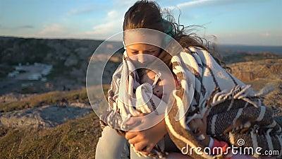Due bambine ammirano il tramonto o l'alba che si siede sulle rocce costiere sulla spiaggia nordica video d archivio