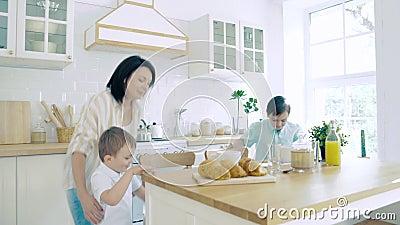 Due bambini felici che corrono da mamma per colazione in cucina stock footage