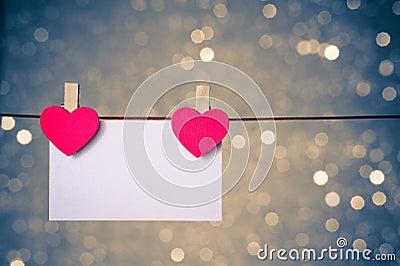 Due cuori rossi decorativi con la cartolina d auguri che appende sul fondo leggero blu e dorato del bokeh, concetto del giorno di