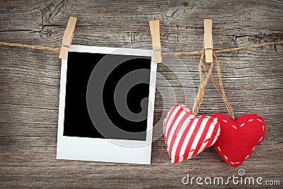 Due cuori rossi e foto istante in bianco