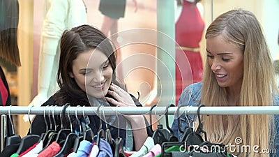 Due donne che esaminano i vestiti sulla ferrovia nel centro commerciale video d archivio