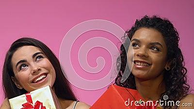 Due donne multietniche che tengono i giftboxes e che sognano delle feste, fine su archivi video