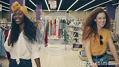 Due giovani donne camminano lungo il negozio con un carrello video d archivio