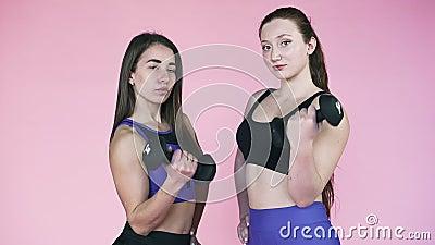 Due giovani ragazze atletiche stringono la mano a dei gusci su uno sfondo rosa Idoneità e sport Movimento lento archivi video