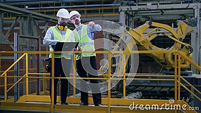 Due impiegati stanno parlando in un interno industriale moderno vicino a un'apparecchiatura robotica stock footage