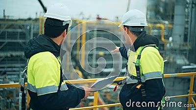 Due lavoratori del gas e del petrolio che duscussing all'industria della raffineria stock footage