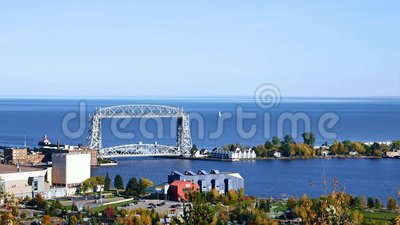 Duluth Aerial Lift Bridge and Lake Superior on a clear afternoon. A sailboat is seen in Lake Superior beyond the Duluth, Minnesota iconic Aerial Lift Bridge on a stock video footage